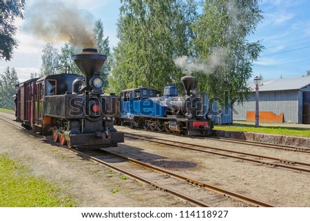 Two narrow-gauge steam trains at the old station. Jokioinen Museum Railway,  Minkio, Finland - stock photo