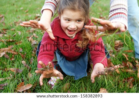 Two naughty sisters young girls playing with muddy hands in a park with green grass and dry leaves during an autumn winter day, holding their dirty hands and showing them. - stock photo