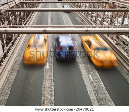 Two New York city taxis speeding across the Brooklyn Bridge surround a small blue car. Note that the cars show motion blur. - stock photo