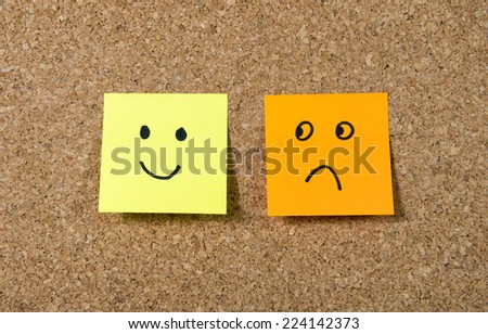 two notes stuck on message cork board  with smiley and sad cartoon face expression in happiness versus depression and smile against adversity concept - stock photo