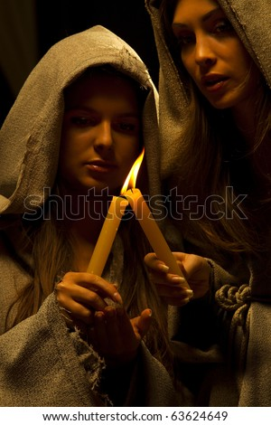 Two nuns  praying with candles in their hands - stock photo