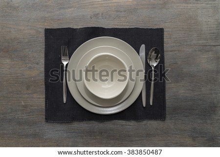 Two off-white plates and a bowl with fork, knife and spoon on a black placemat on a wooden table - stock photo