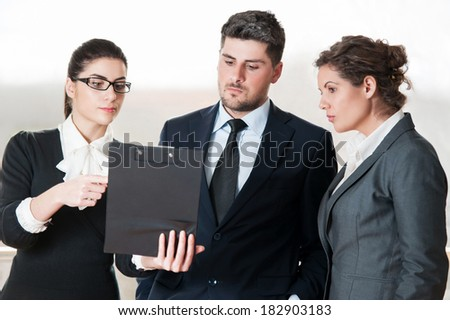 Two office colleagues and one business man talking over clipboard - stock photo