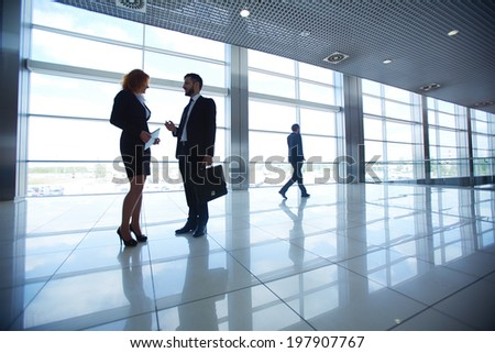 Two office workers discussing ideas on background of businessman - stock photo