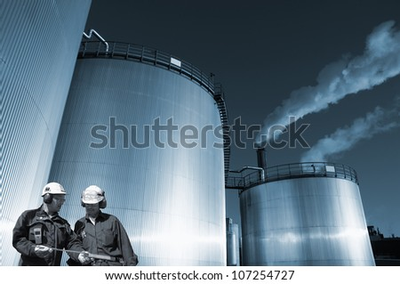 two oil and gas workers, large fuel storage tanks in background, blue toning concept - stock photo