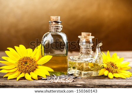 Two oil bottle with sunflower on brown background - stock photo