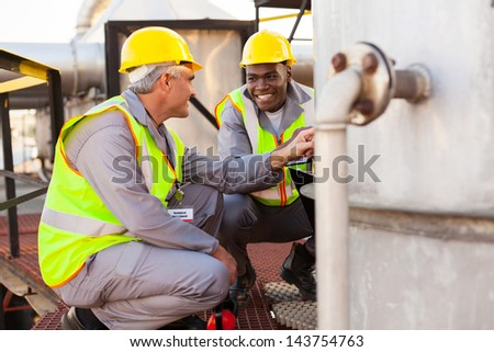 two oil chemical industry technicians working in plant - stock photo