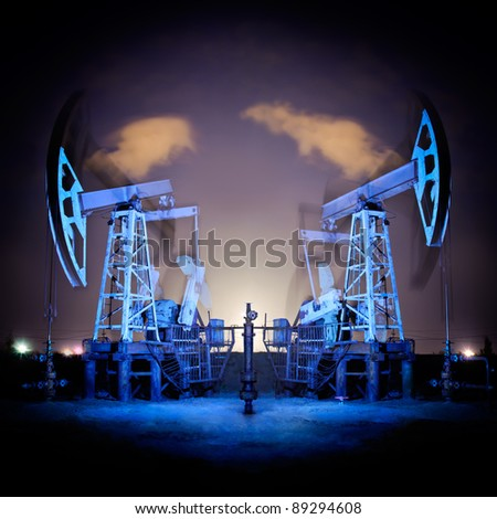 Two oil pumps jack in action. Night view. Long exposure. - stock photo