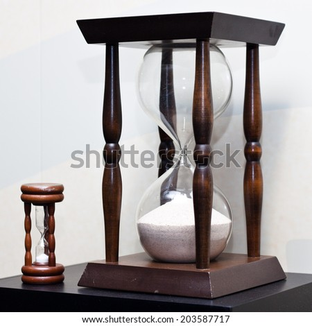 Two old antique wooden sand clock. Big and small sand clock. - stock photo