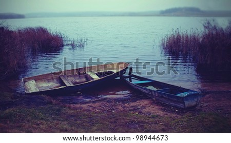 two old dilapidated boat on the lake in autumn - stock photo