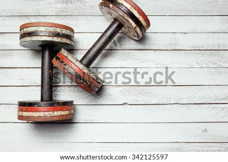 Two old dumbbells on white wooden background. - stock photo