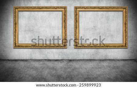 Two old golden frames on gray wall - stock photo