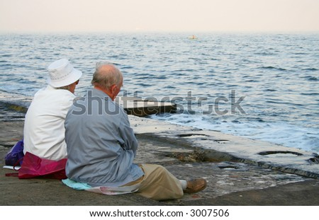 Two old people on the beach - stock photo