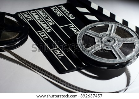 Two old reels of film and cinema clap lying on a light table.  - stock photo