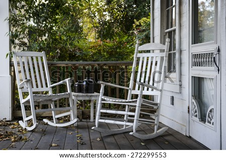 two old rocking chairs on the front porch of an old house - stock photo
