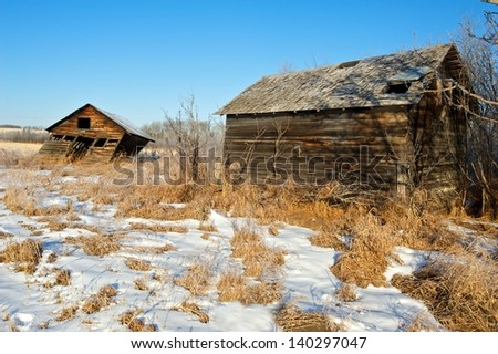 two old sheds in a snowy field - stock photo