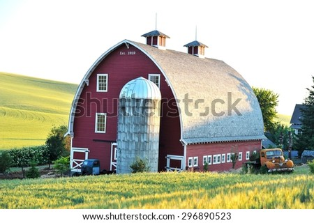 Two old trucks parked on the side of the beautiful red barn with the sunbeams on the wheat field - stock photo