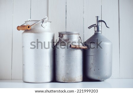 Two old vintage aluminum milk cans  and a siphon, painted white wooden board, rustic background - stock photo