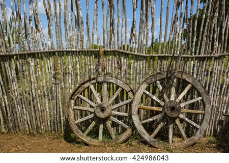 Two old waggon wheels near the wooden fence - stock photo