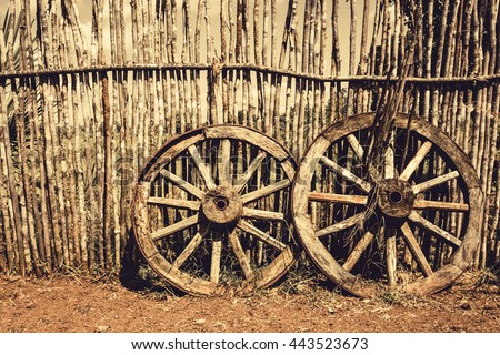 Two old waggon wheels near the wooden fence, filtered with soft pastel colors with filters. Old cart wheel as a symbol of fortune and fate. - stock photo