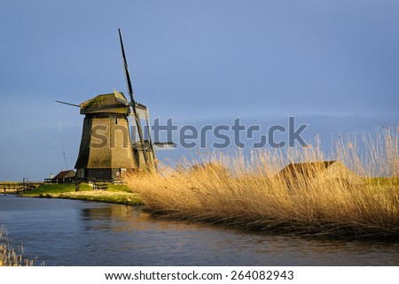 Two old water mills beside a canal of the Eilandspolder in evening light, The Netherlands - stock photo