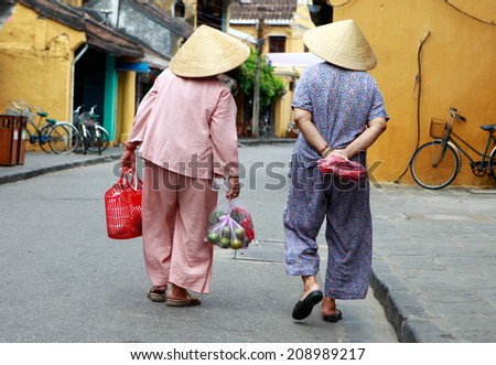 Two old women going home after shopped in the market. - stock photo