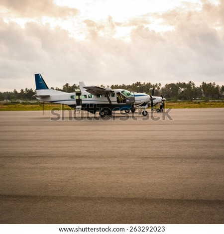 Two older airplanes in the Zanzibar airport at sunrise - stock photo