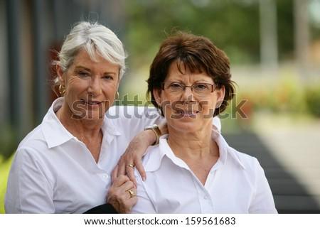 Two older women standing outside - stock photo