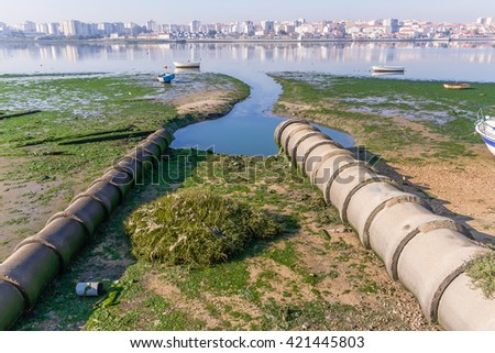 Two open air sewer pipes draining to the Seixal Bay, a Tagus River branch near Lisbon, Portugal. - stock photo