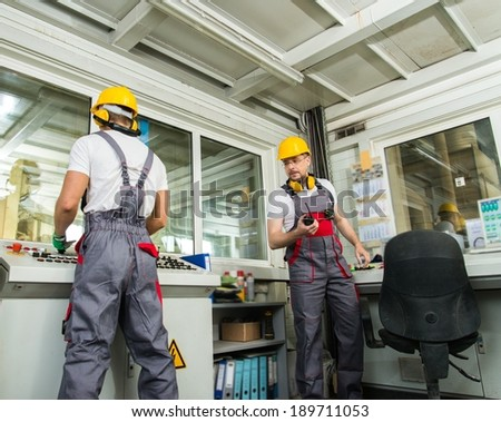 Two operators wearing safety hat in a factory control room - stock photo