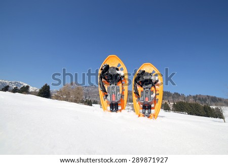 two orange snowshoes in mountains in winter - stock photo
