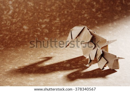 Two origami elephants isolated on craft paper background. - stock photo