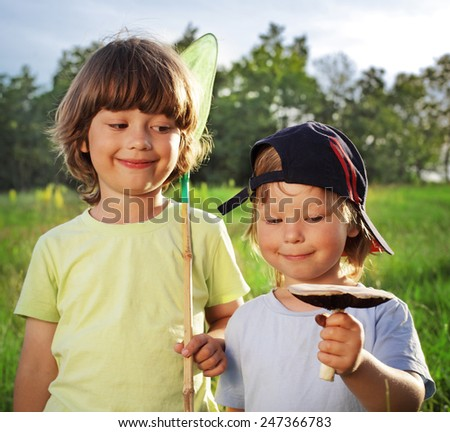 two other children walking rural with mushroom, net - stock photo
