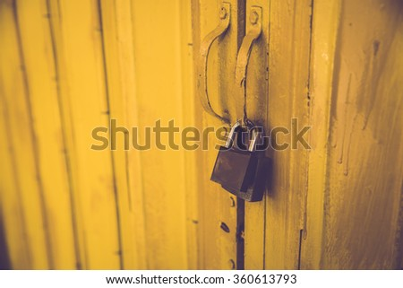 Two pad locks on yellow metal door. Vintage filter. - stock photo