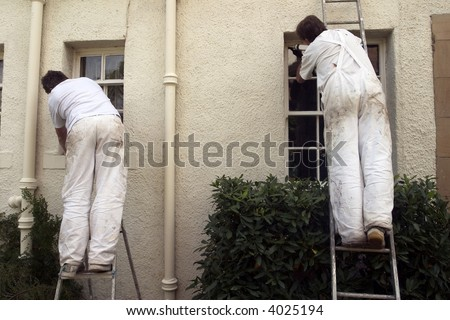 Two painters decorating the exterior of a house. - stock photo