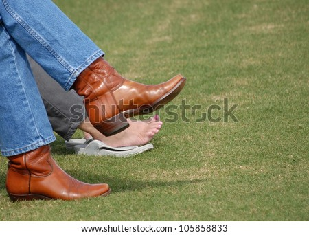 Two pair of feet are in stark contrast with a man's rough and tough look in jeans and cowboy boots and a woman's pampered and pedicured bare feet as they relax on a manicure green lawn - stock photo