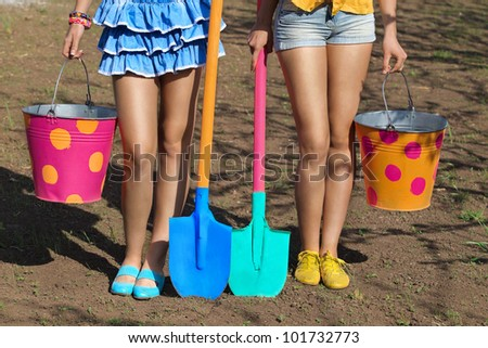 Two pair of female legs with buckets and shovels on garden - stock photo