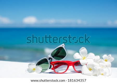 Two pair of sun glasses on a beach table on blue ocean background - stock photo