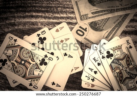 Two pairs and three of a kind vintage poker cards with money on a wooden background  - stock photo