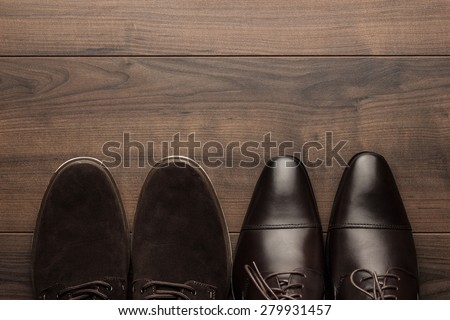 two pairs of brown shoes on the wooden table - stock photo