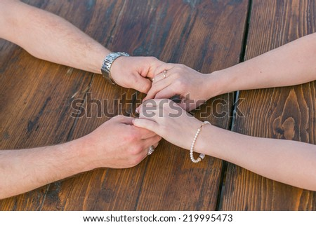 Two pairs of hands holding each other gently - stock photo