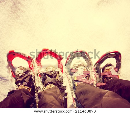 two pairs of snowshoes with copy space toned with a retro vintage instagram filter  - stock photo
