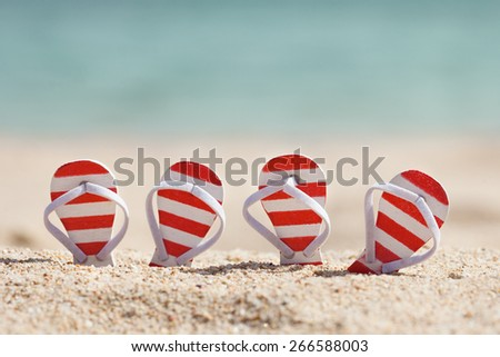 Two Pairs Of Striped Flip-flops On Beach - stock photo