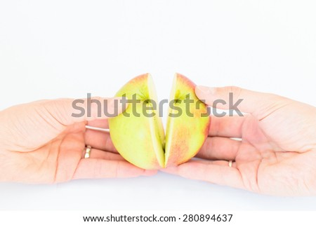 Two palms (male and female) are splitting the ripe apple - stock photo