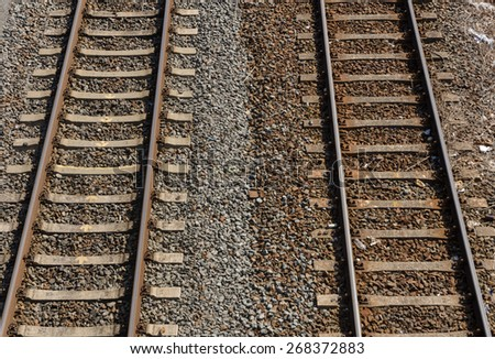 two parallel railway tracks with two colored gravel and stones in between - stock photo