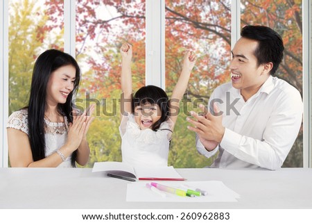 Two parents giving applause to their daughter after finishing her homework - stock photo