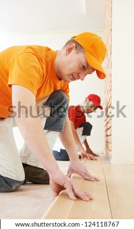 Two parquet carpenter workers installing wood board during flooring work - stock photo