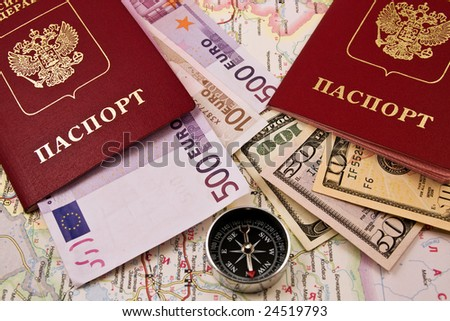 Two passport with the money on a map and compass - stock photo