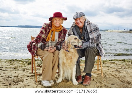 Two pensioners and their pet spending weekend together by seaside - stock photo