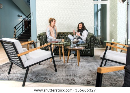 Two people, a man and a woman, sitting on a chesterfield couch in a trendy, retro styled, lobby of a theater, talking vividly with gestures - stock photo